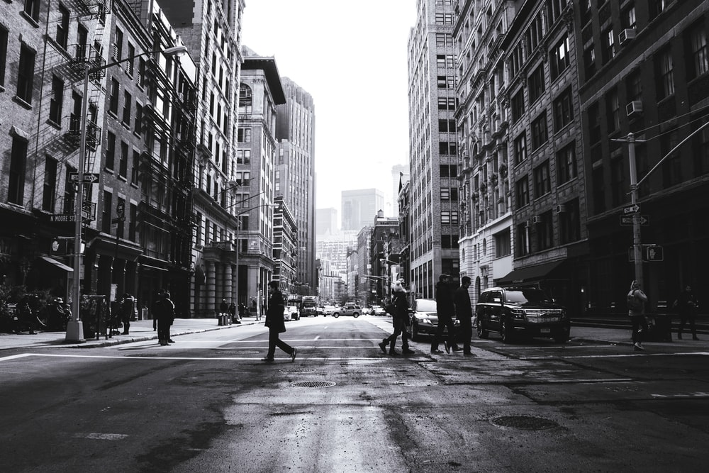 grayscale photography of people crossing the street