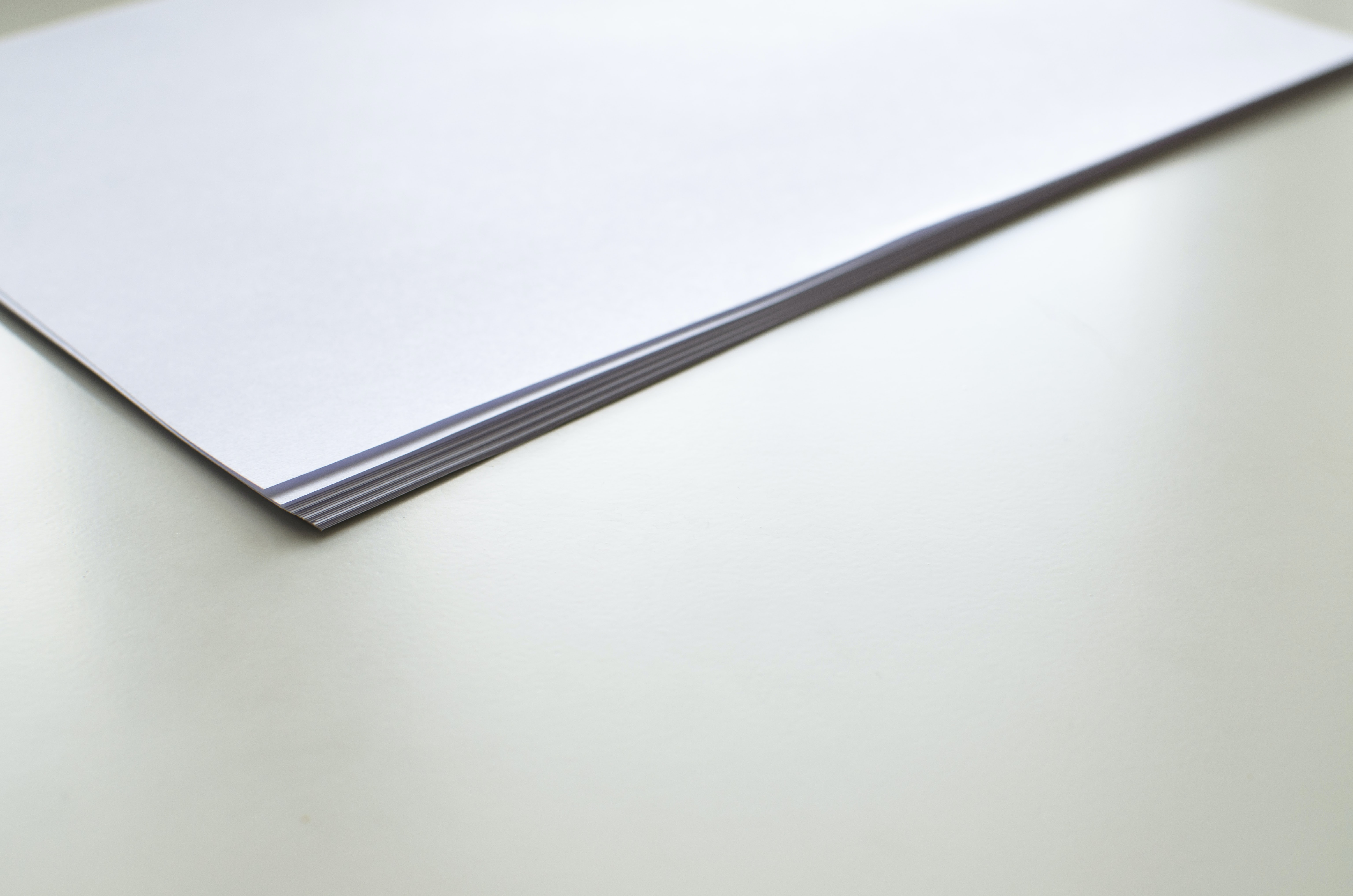 A stack of white paper sheets on a white surface
