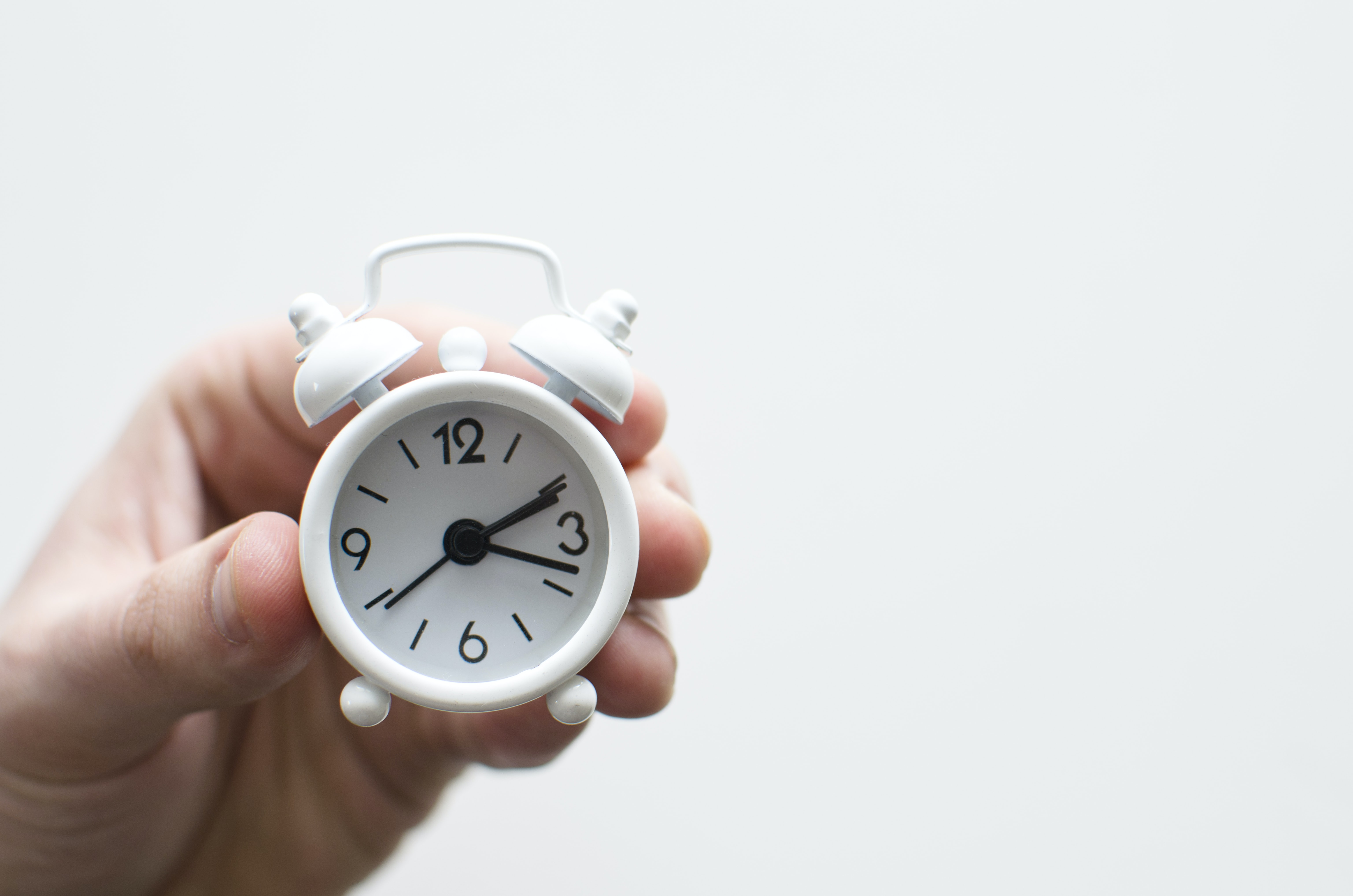 A hand holding a tiny white alarm clock