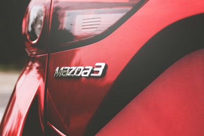 closeup photography of red mazda 3 vehicle mazda teams background