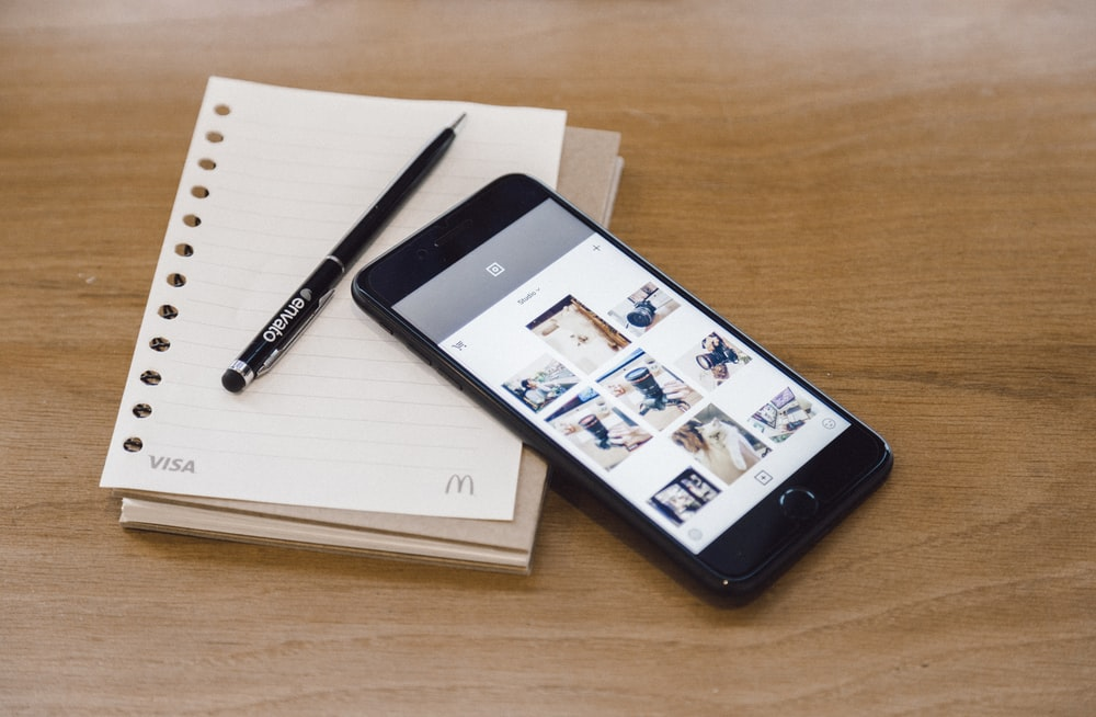 A smartphone, notebook and pen.