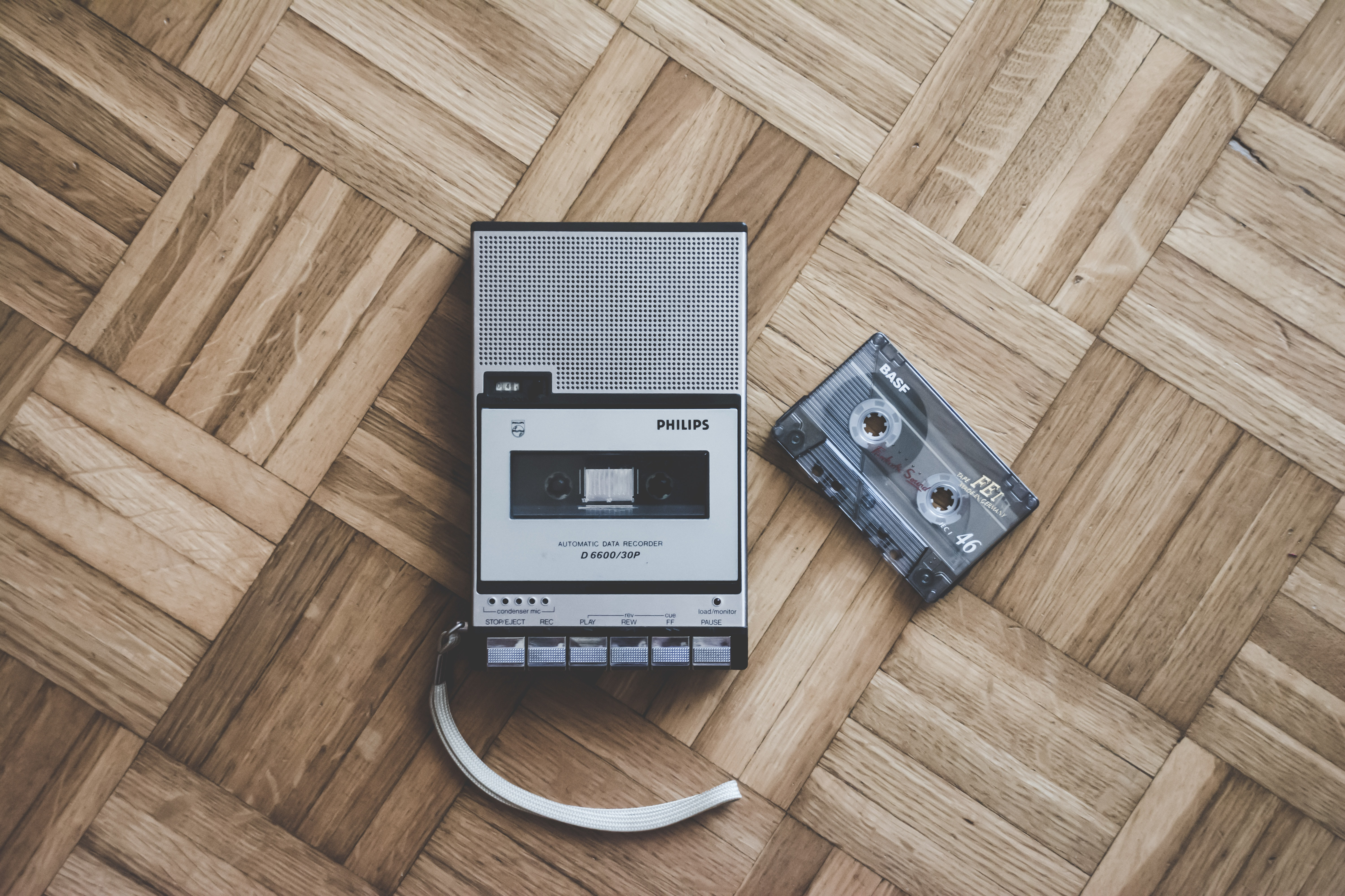 An old Philips cassette player and tape laying on a wooden floor in Italy