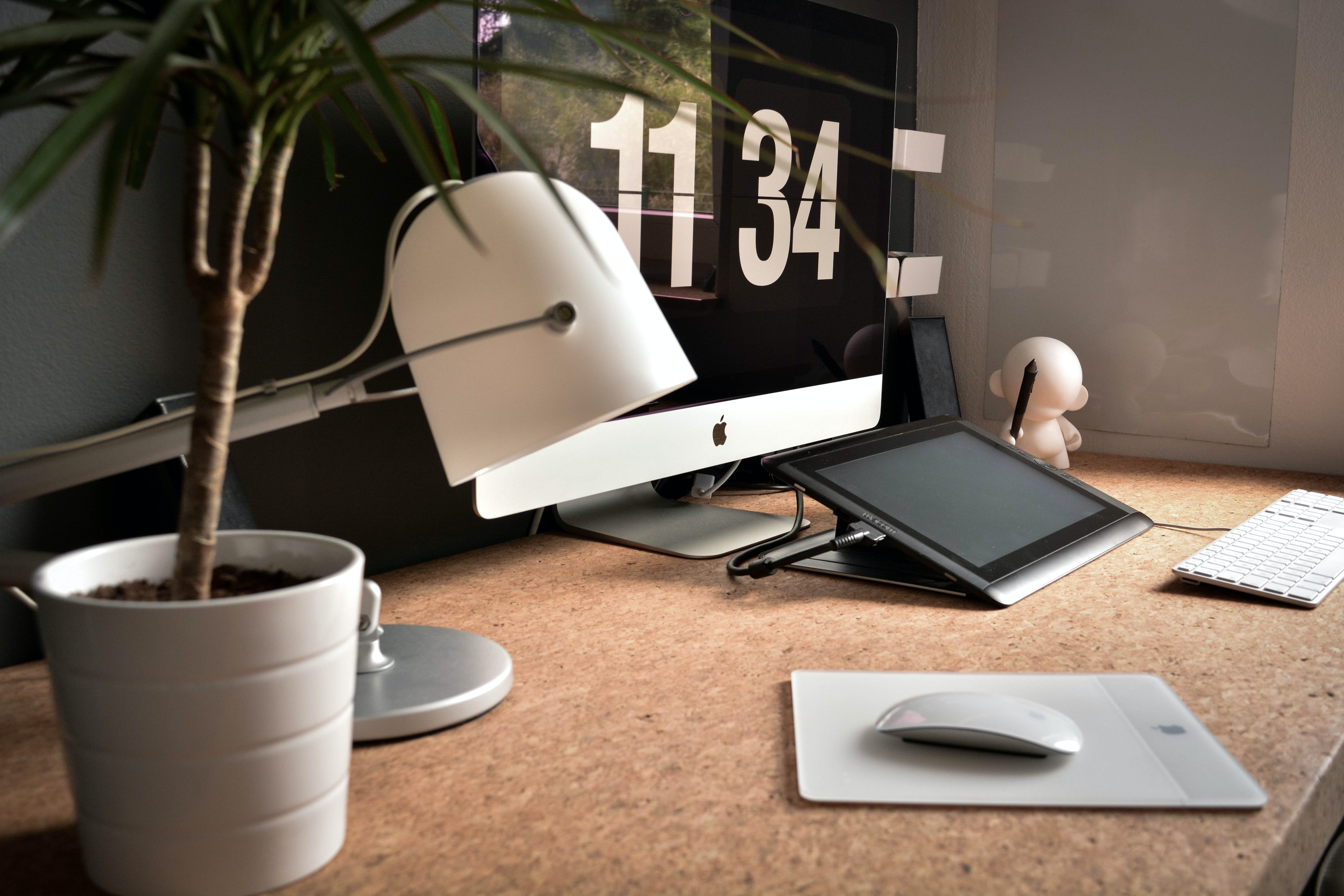 Office space with a Mac computer, lamp, tablet, mousepad, keyboard, and plant