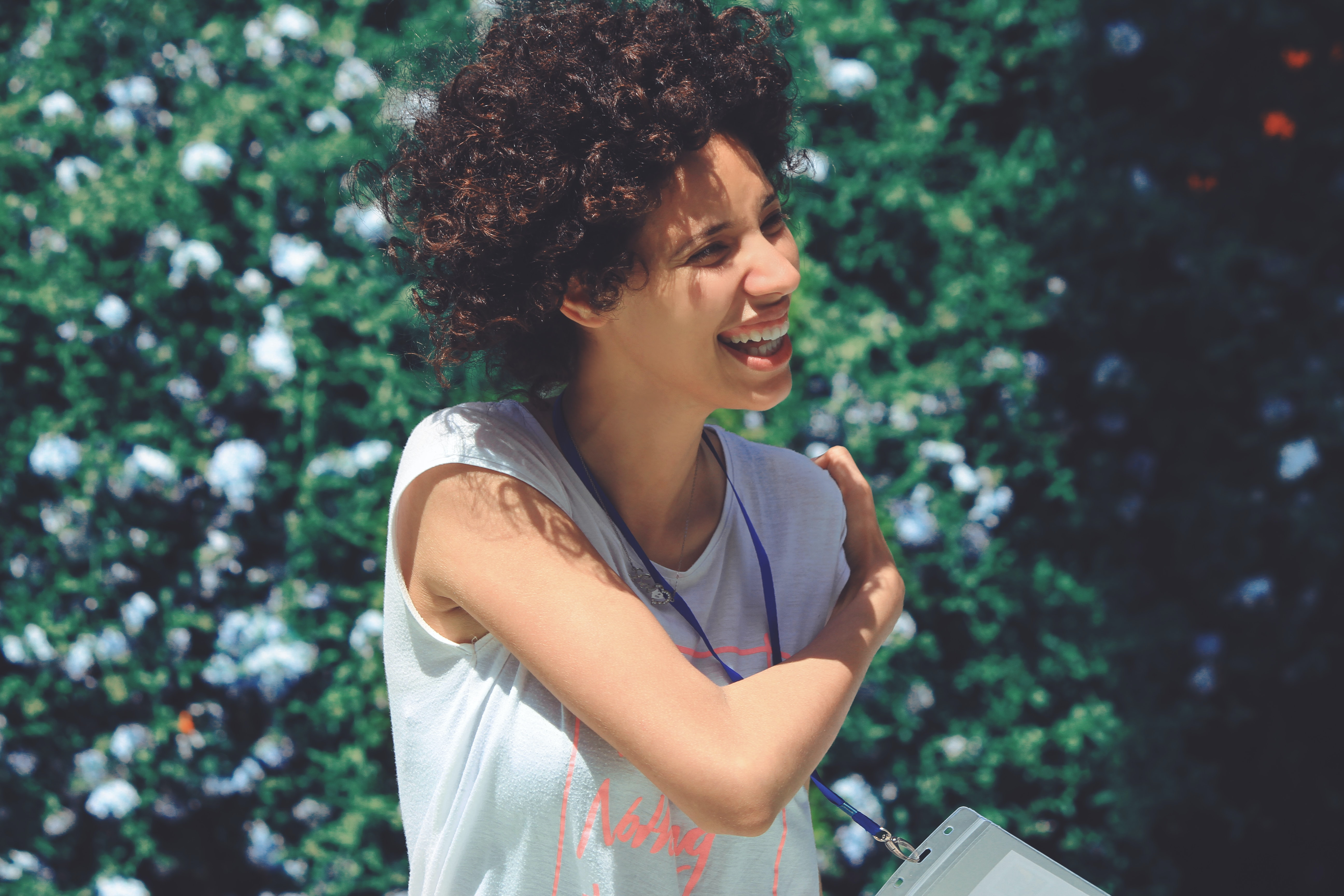 Woman with curly hair laughs while wrapping her arm around to her shoulder in front of greenery