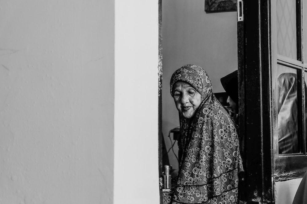 grayscale photo of woman between doors