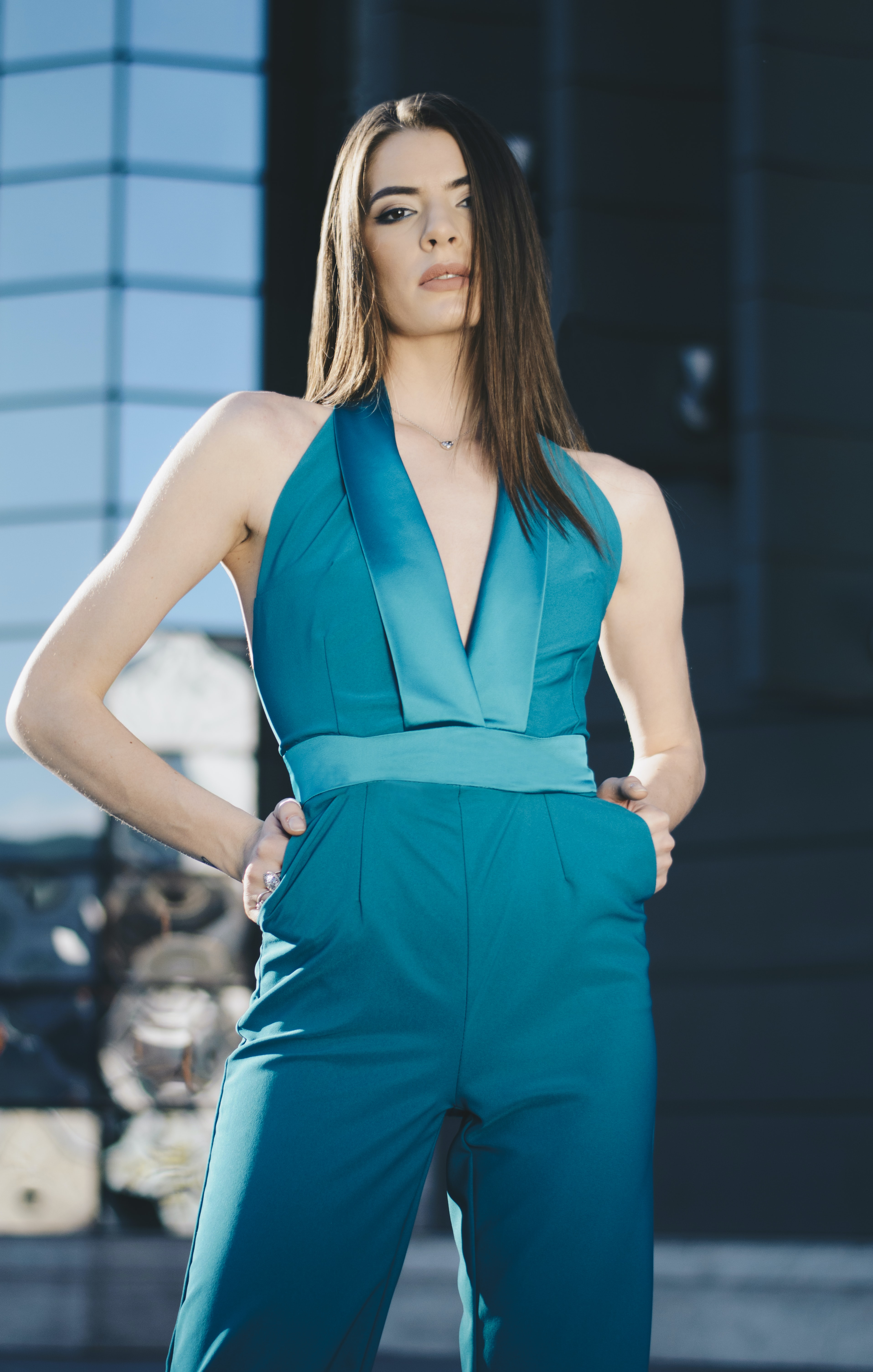 A fashion model wearing a blue structured jumpsuit