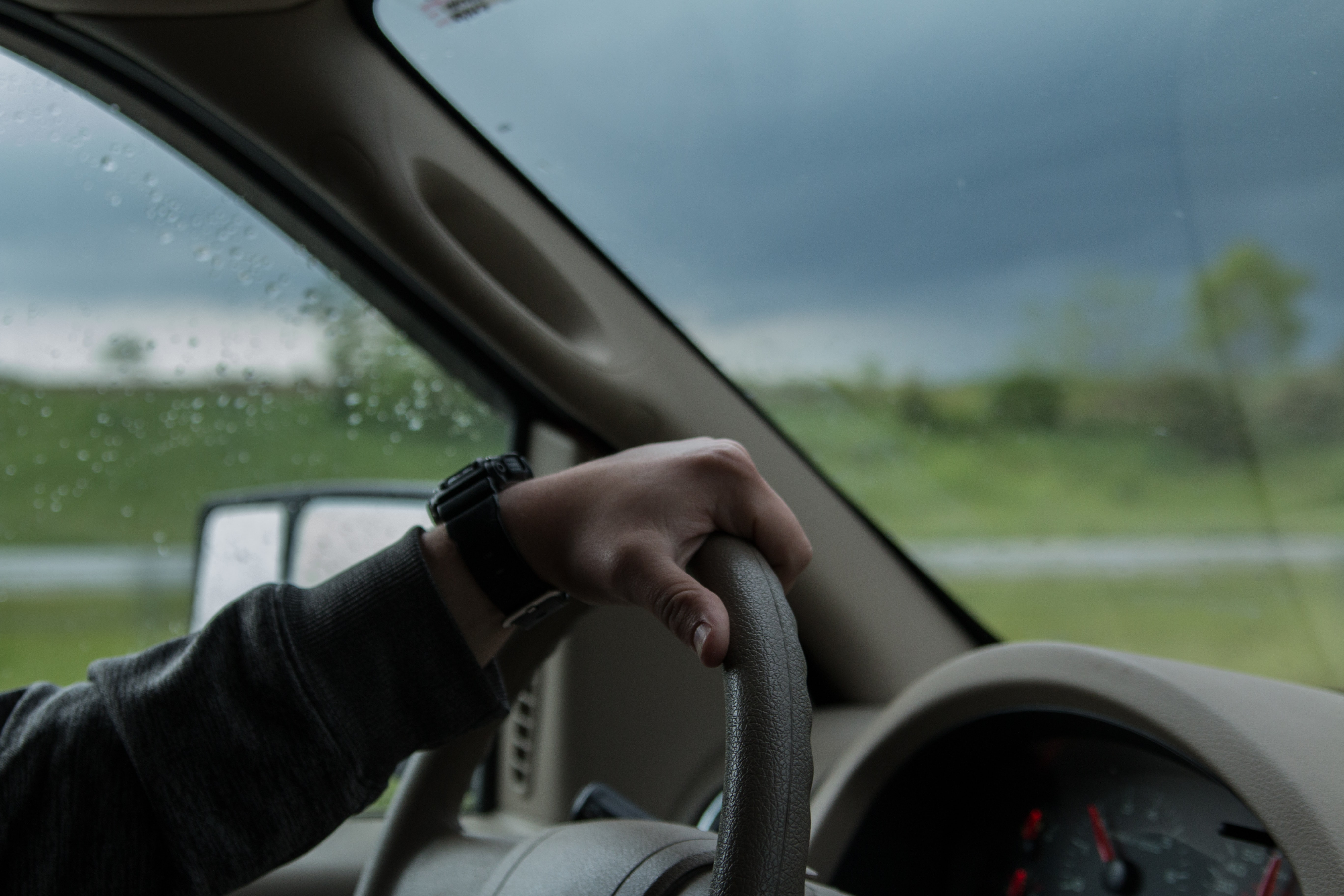 A close-up of the steering wheel with the driver's hand during a rainy day.