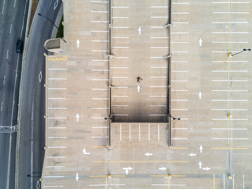 person lying on gray concrete parking area in aerial photography