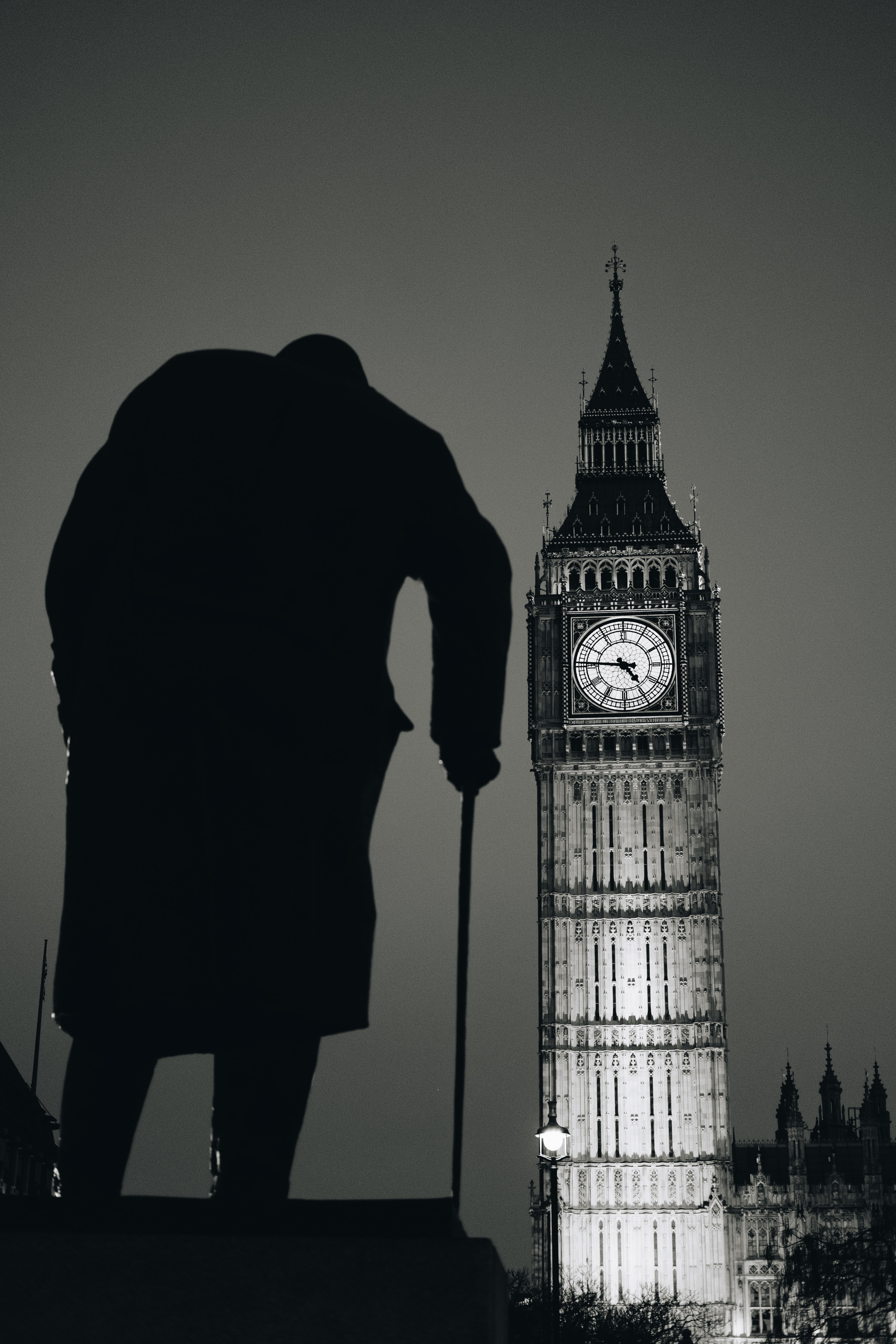 Silhouette of a man with a cane far in the foreground with Big Ben in the background