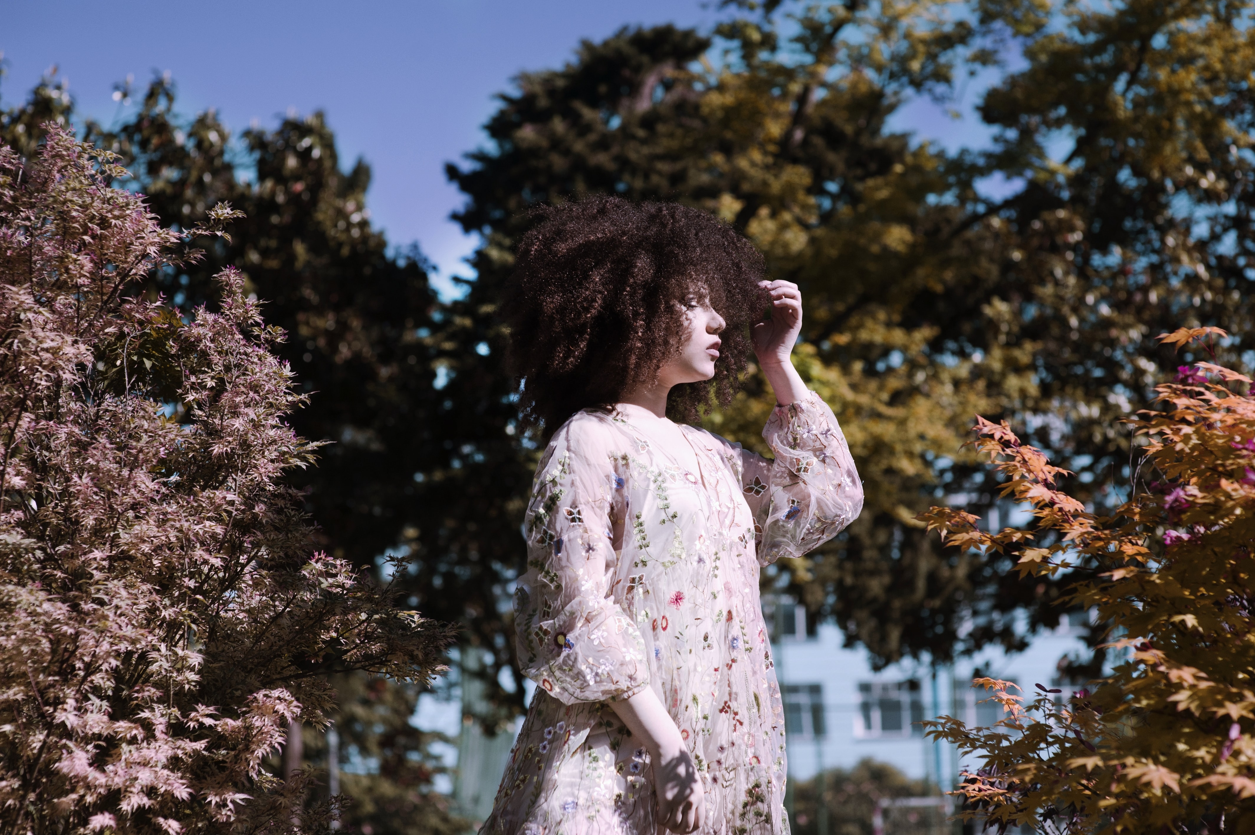 A woman in a pink dress touches her curly hair among trees in Batumi