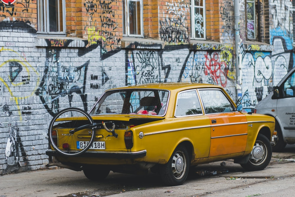 vintage yellow coupe with unicycle on back park near graffiti wall