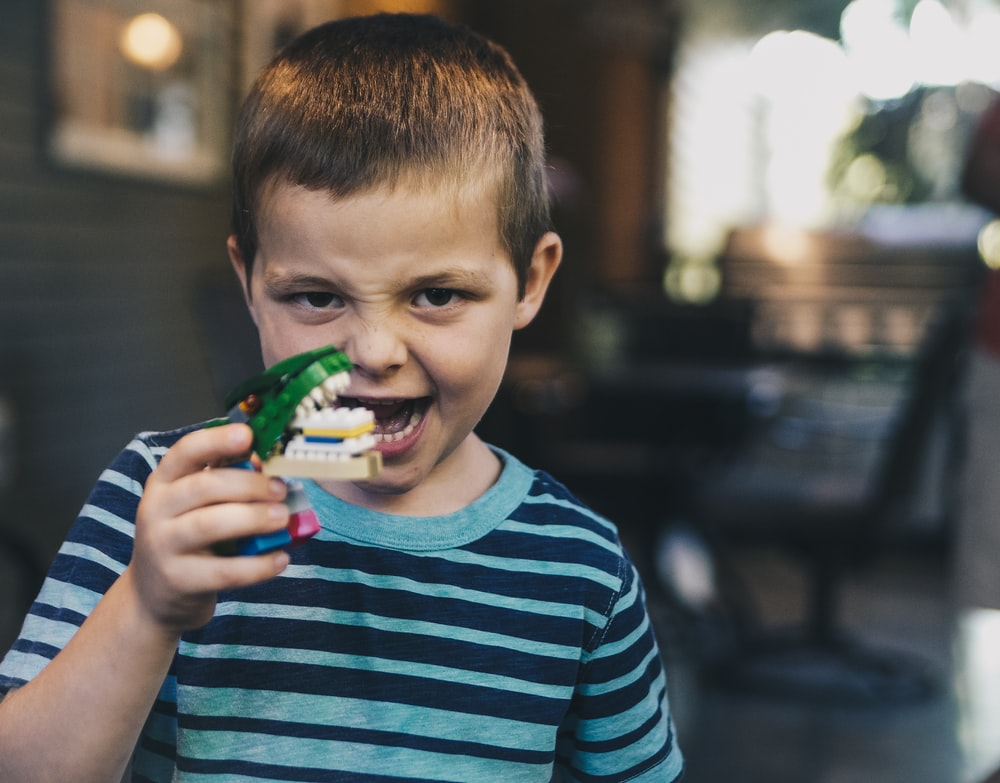 boy wearing teal and black striped t-shirt holding toy