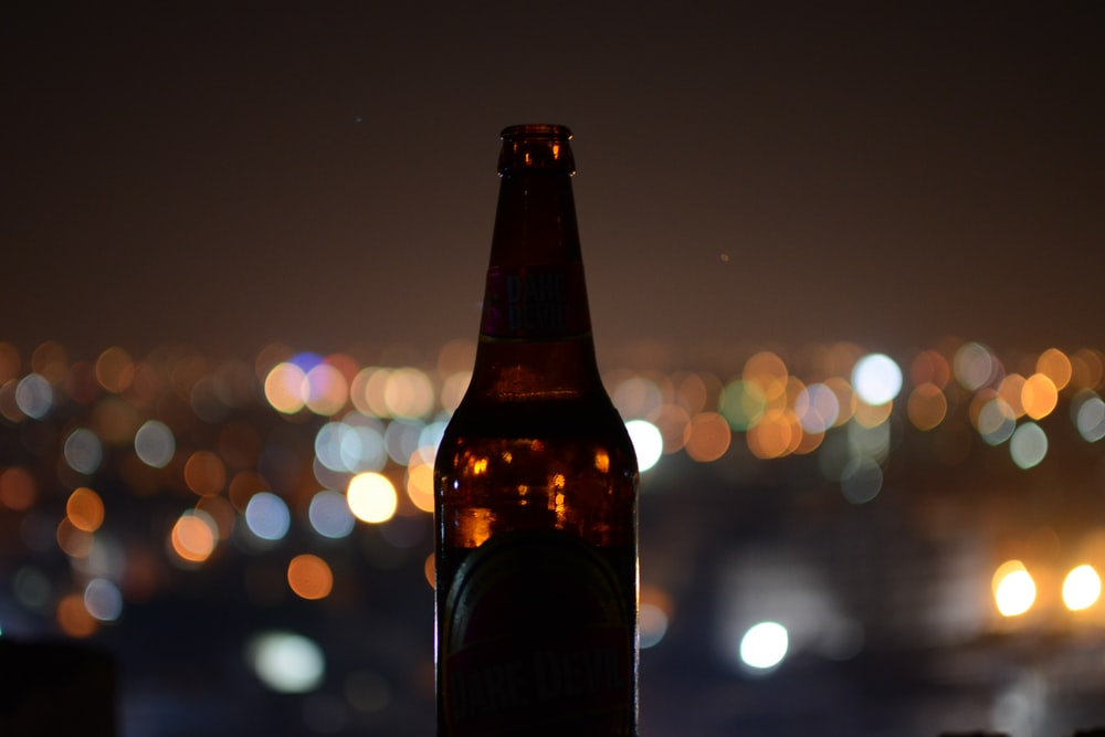 shallow focus photo of brown glass bottle