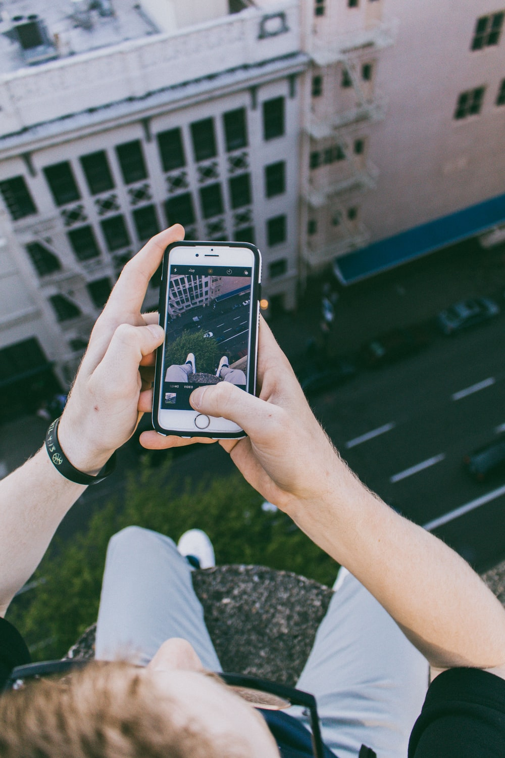man taking photo above building