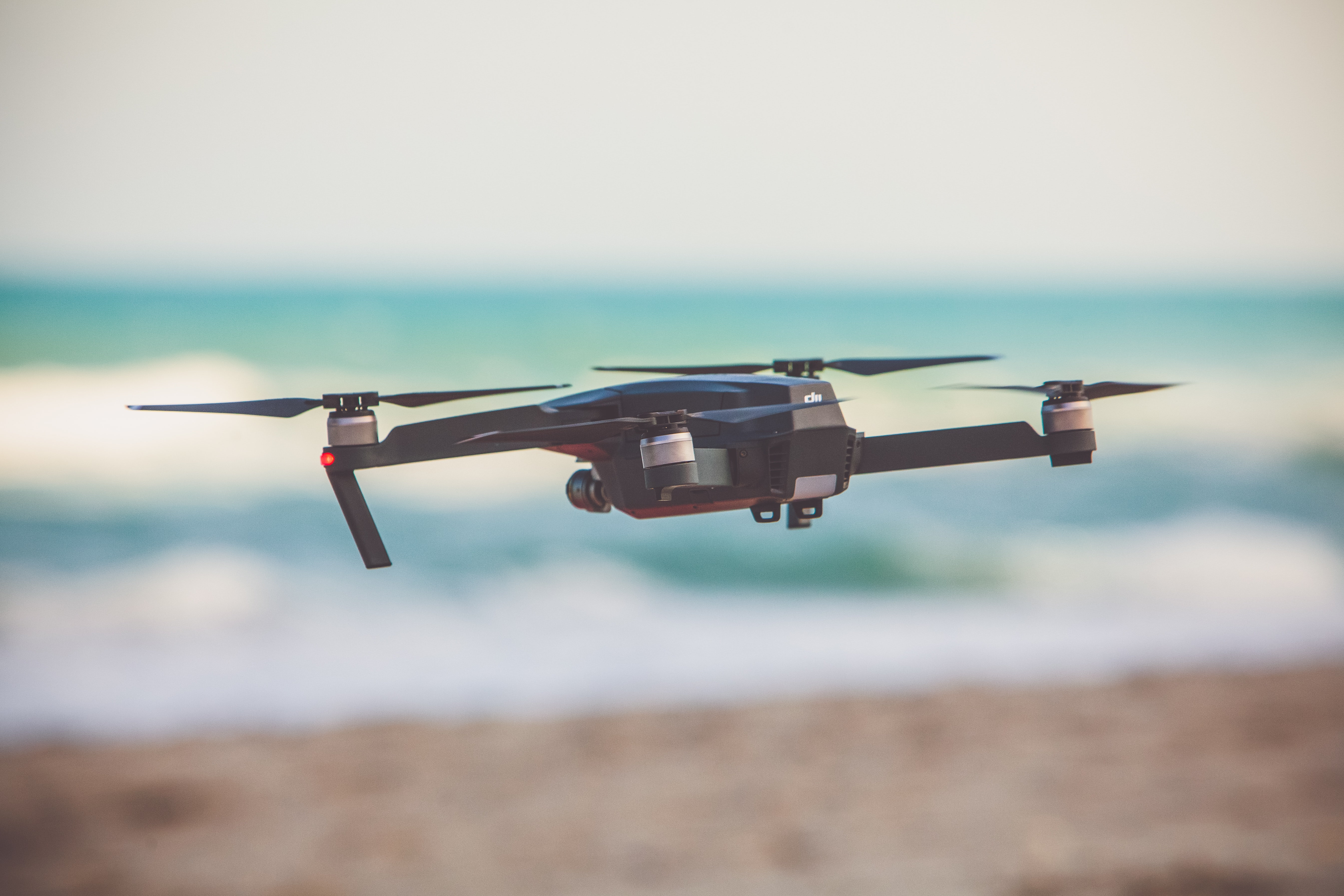 A drone hovering at the beach with a blurred background.
