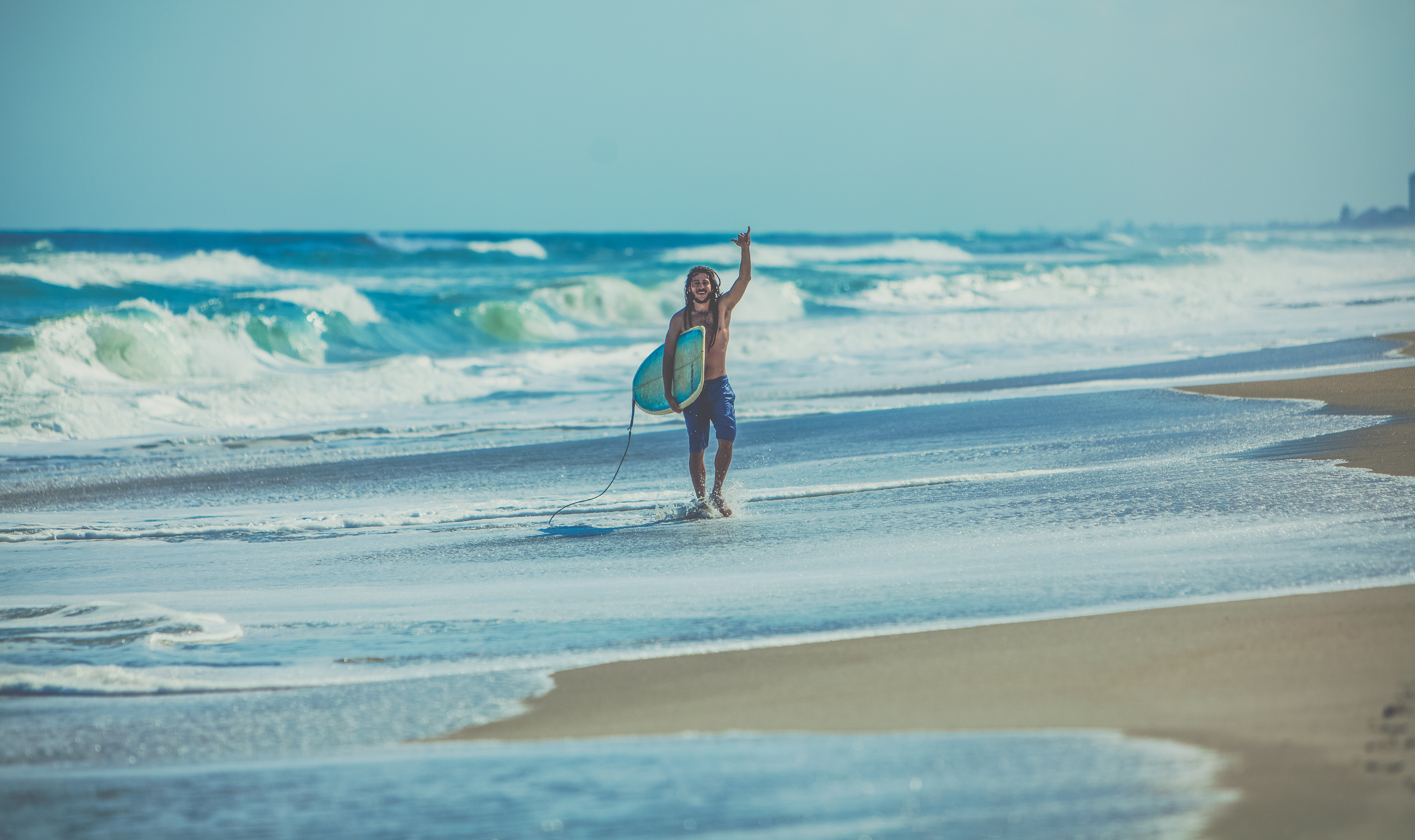 Surfer with raised hand on the sandy shore in Melbourne