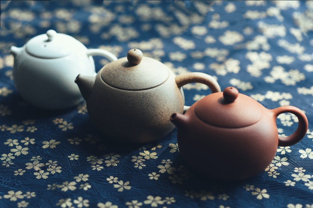 three assorted-color teapots