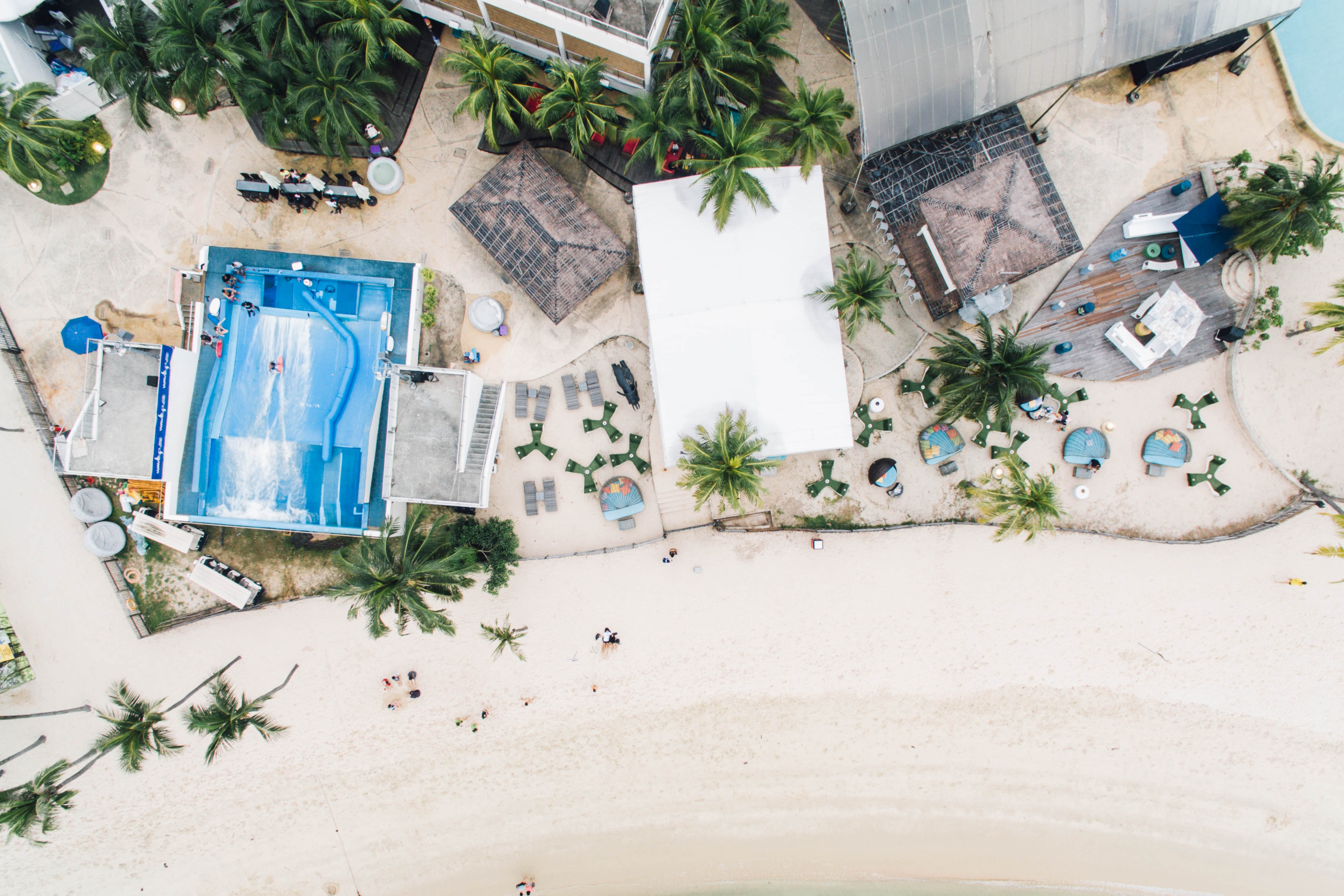 Drone aerial view of the coastal resort buildings on the sand beach at Sentosa