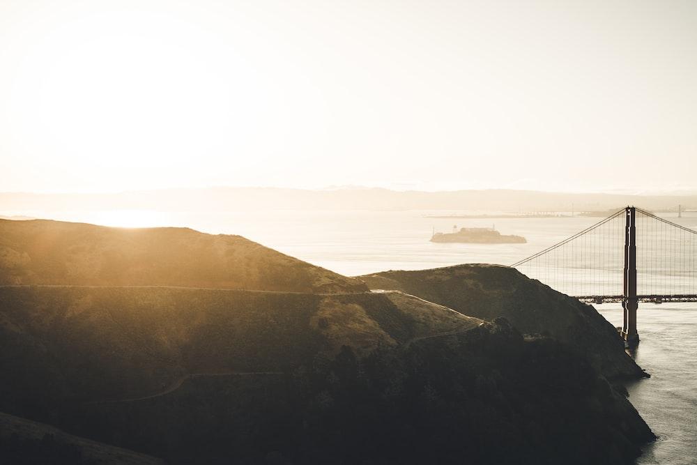 bridge near mountain at golden hour
