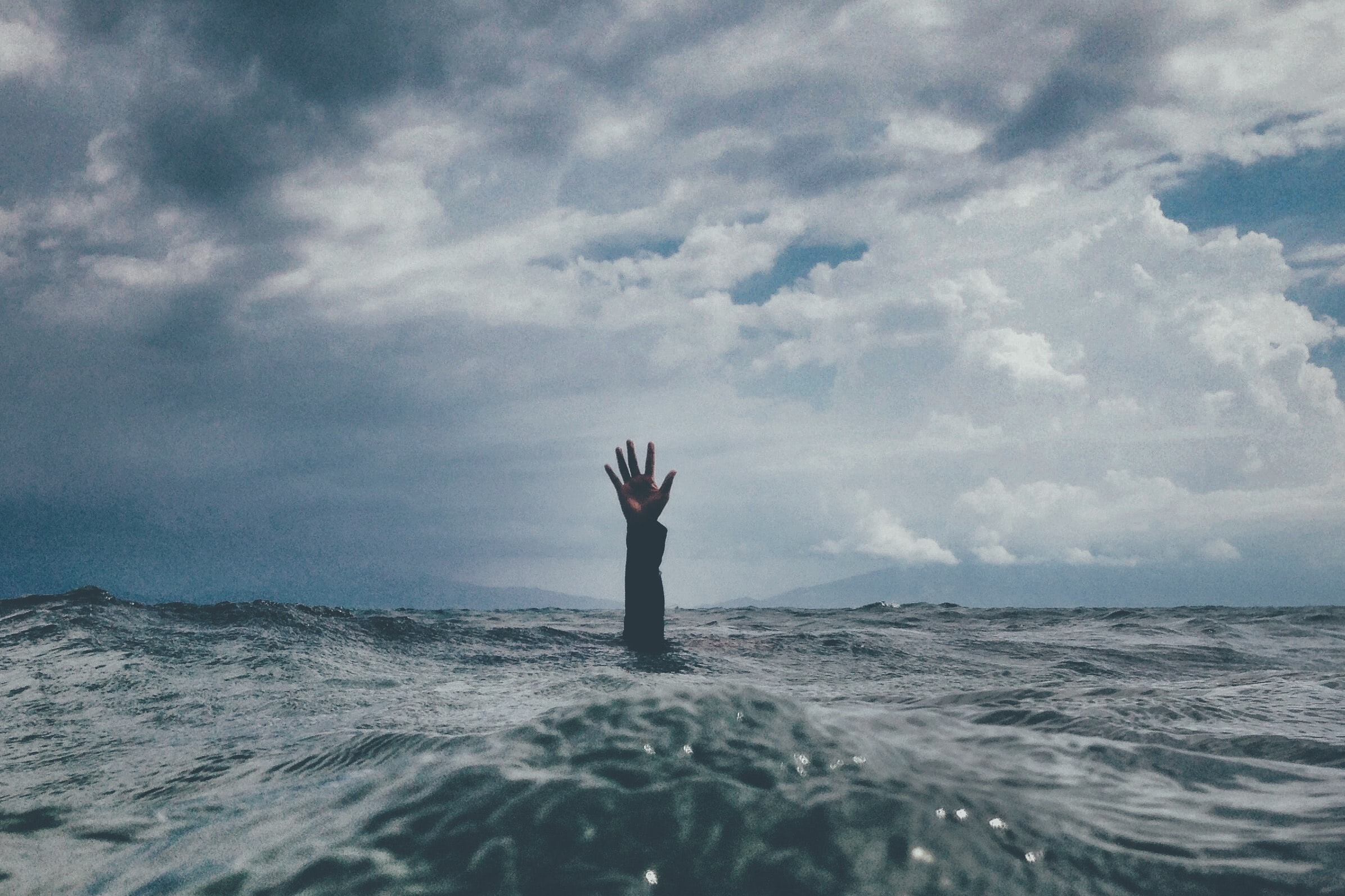 photo of person reach out above the water