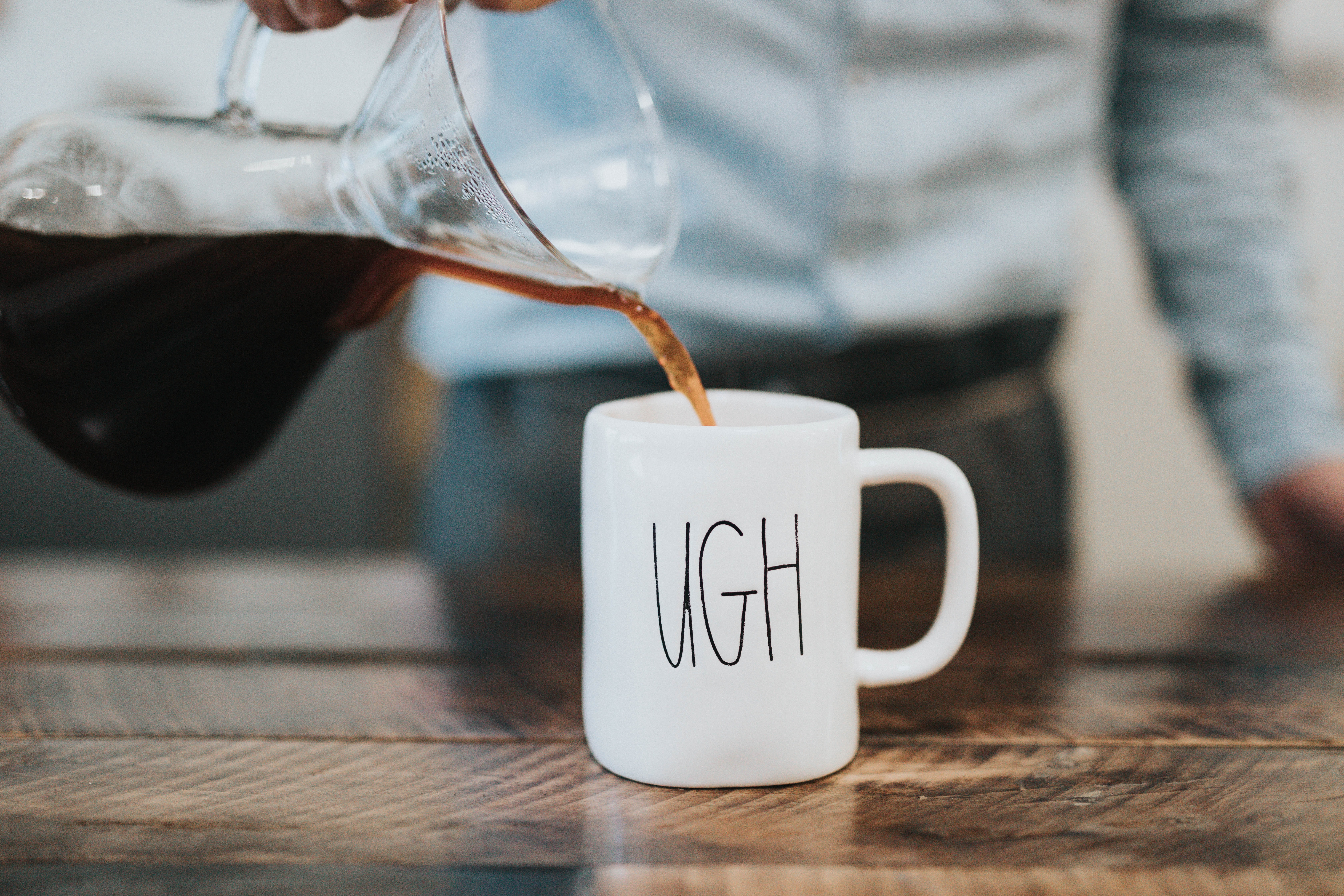 A barista pouring coffee into a mug that says ugh on it at Bar Nine