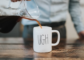 man pouring coffee in white mug