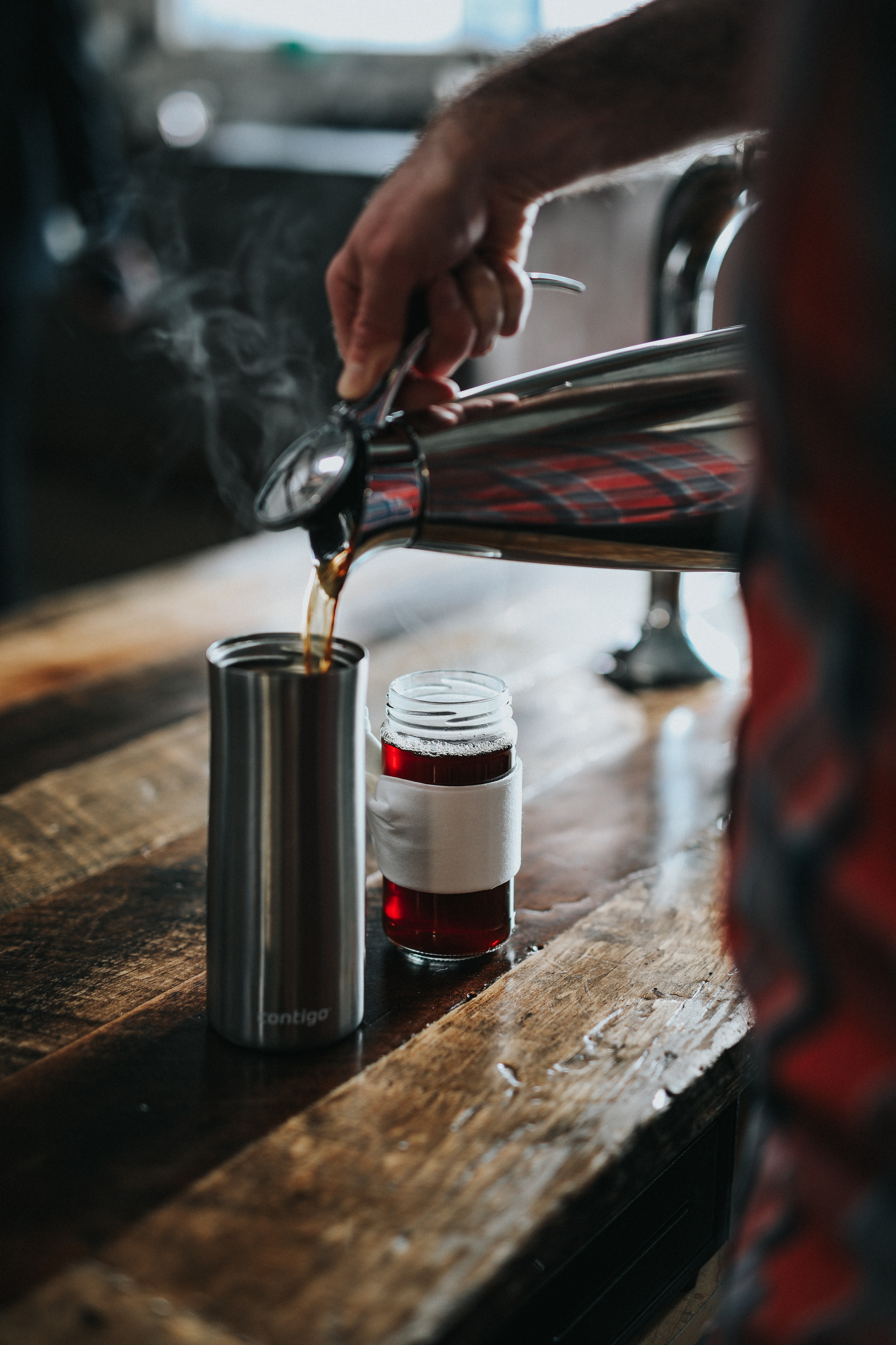 person pouring coffee onto metal tumbler