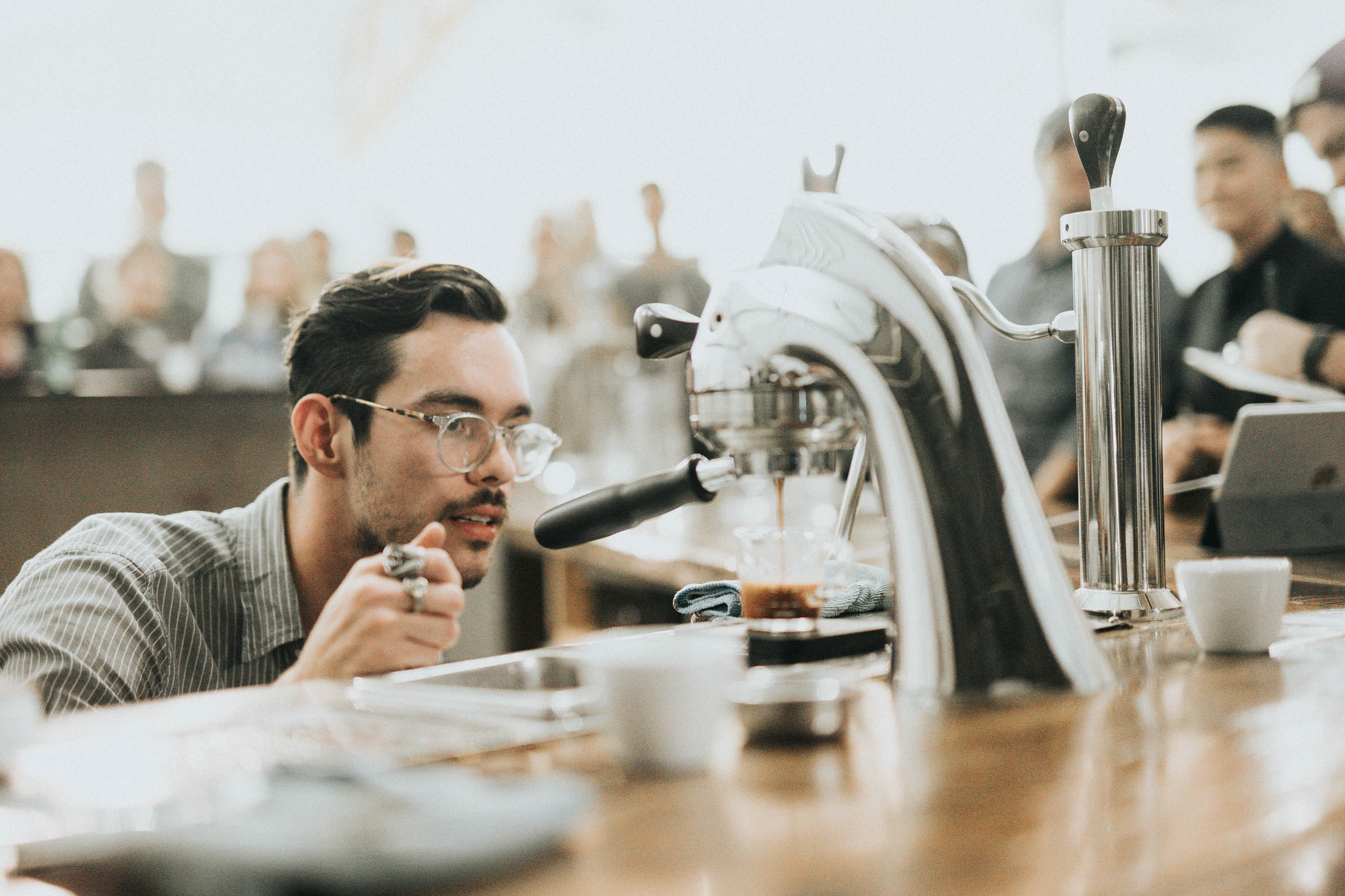 Barista looking at an espresso machine while making coffee