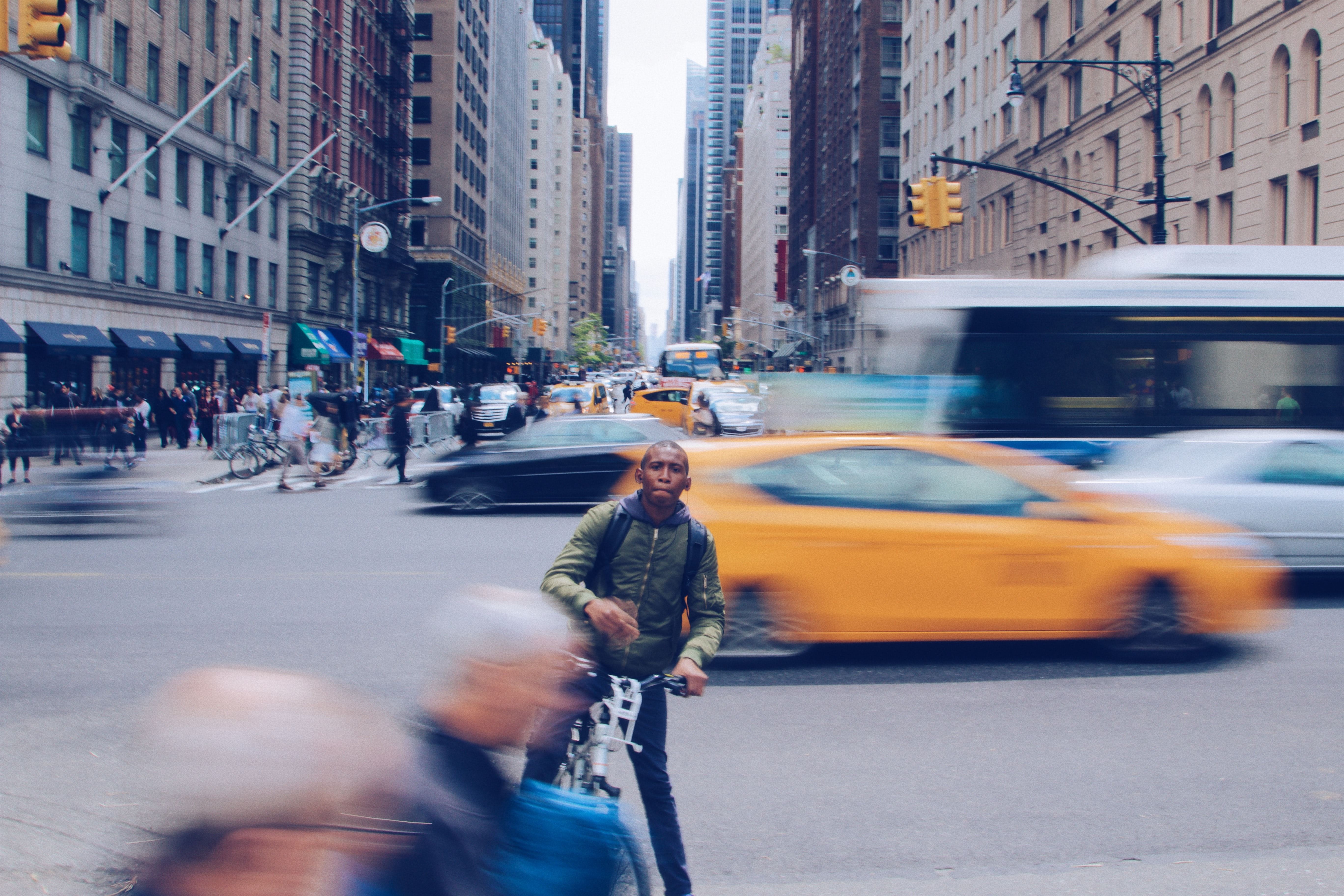 A man on a bicycle stopping near the sidewalk in a busy New York street