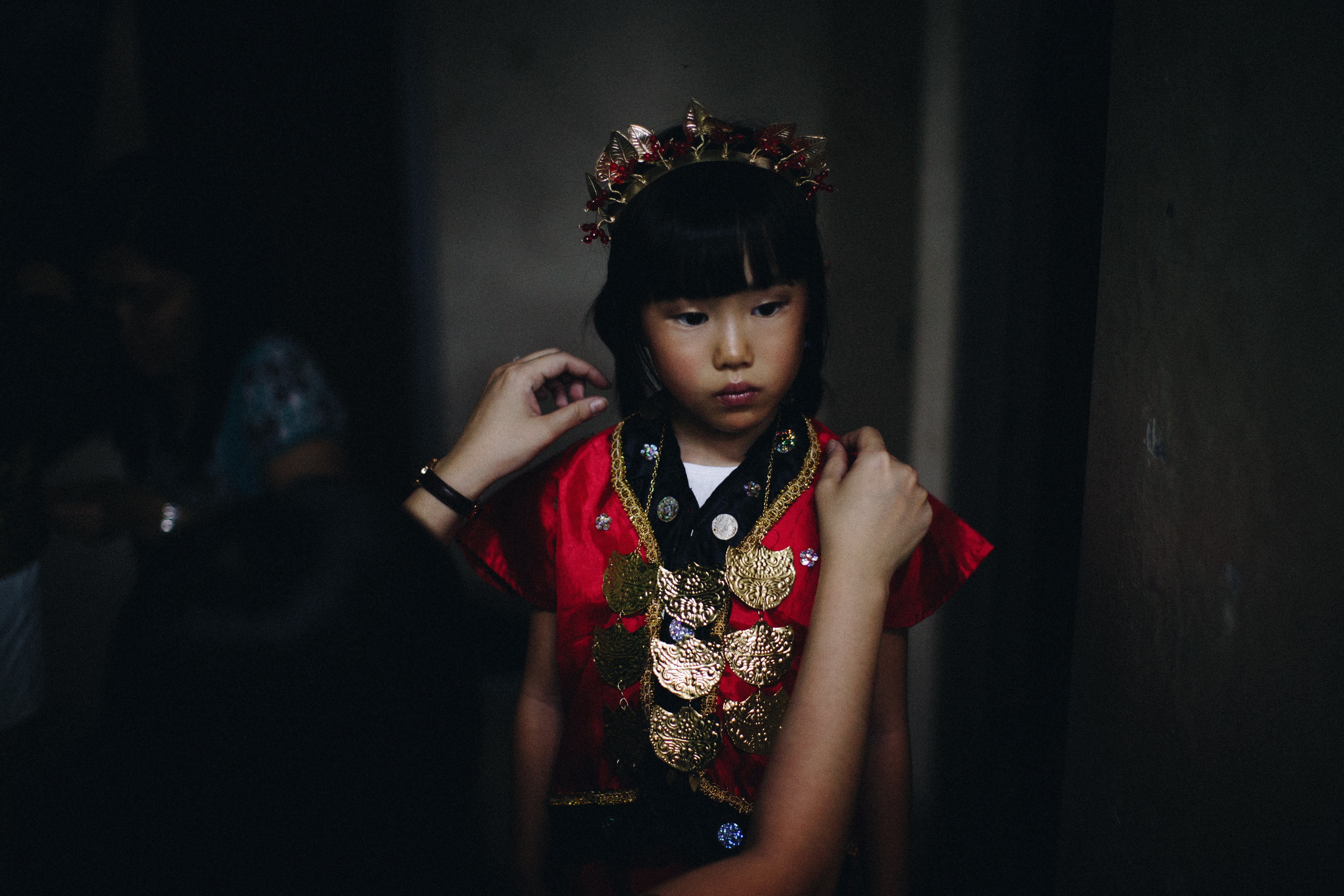 A person styles a child in a headdress and red traditional formal clothing