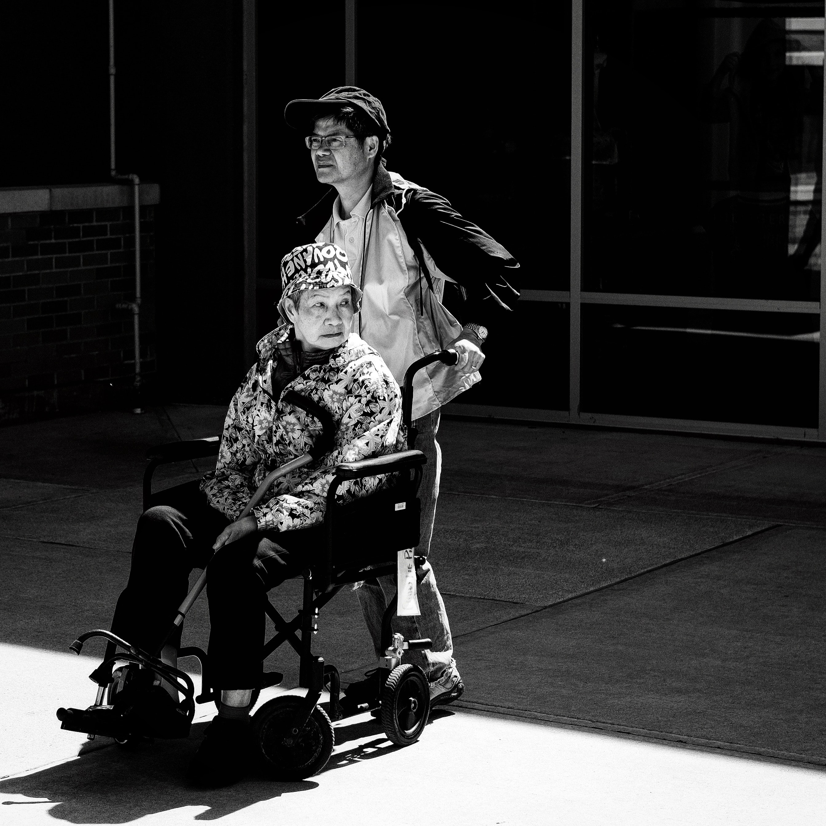 Black-and-white photo of a man pushing a woman in a wheelchair