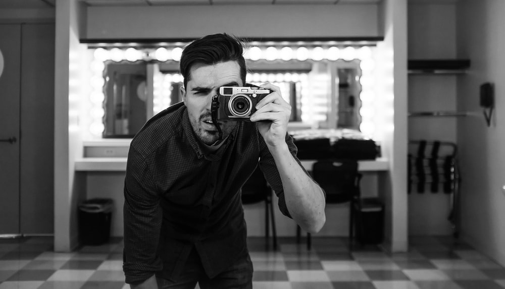 man holding camera bending down in grayscale photography