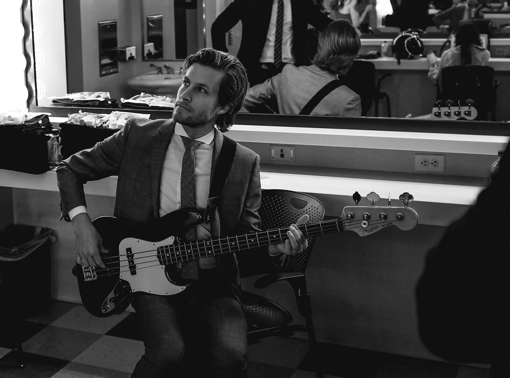 grayscale photography of man wearing suit holding guitar