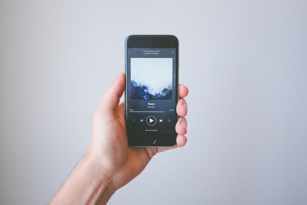 Smartphone held in hand displays Spotify music application