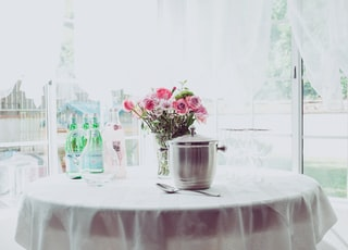pink petaled flower centerpiece on white table beside container