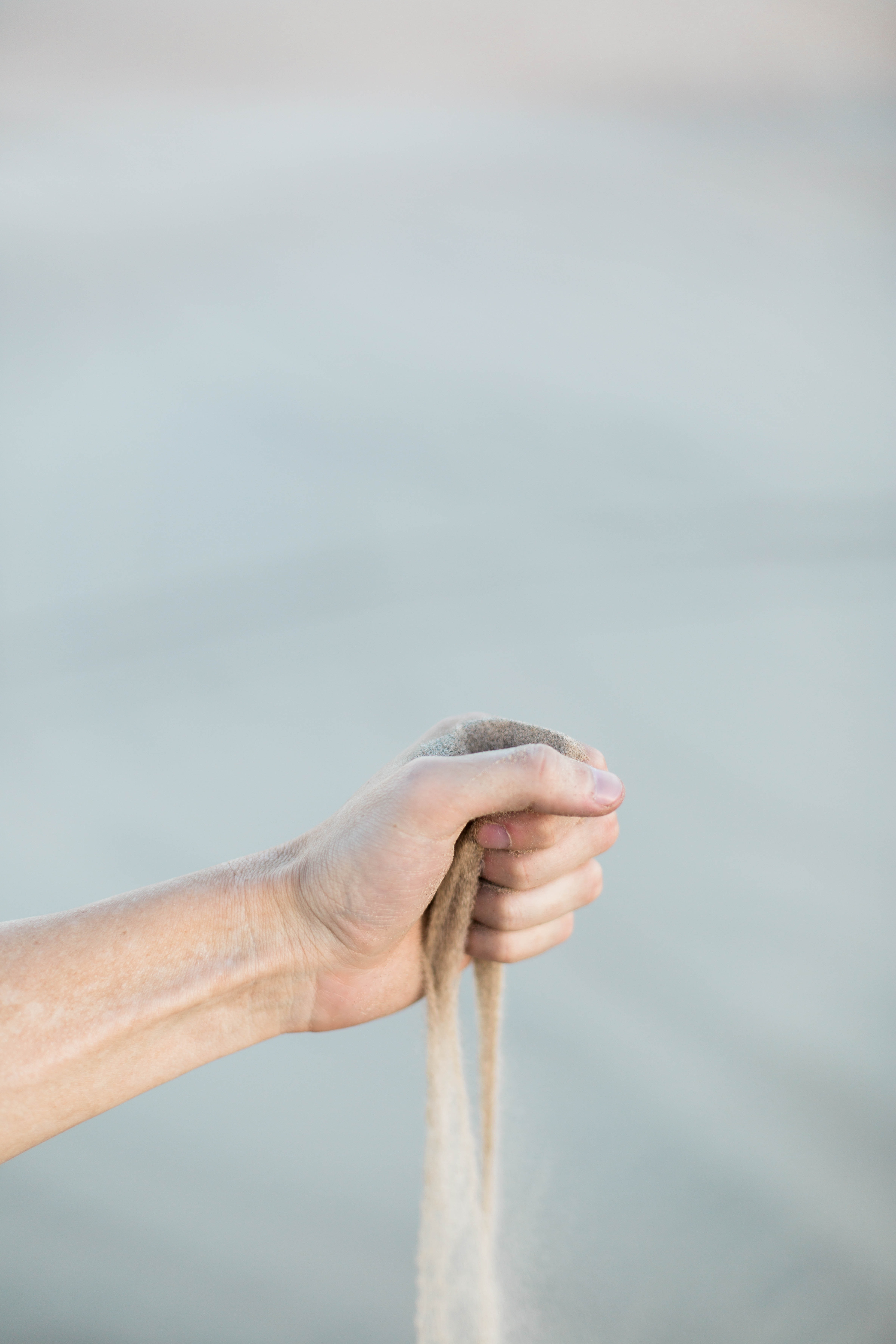 selective focus photography of person holding sand