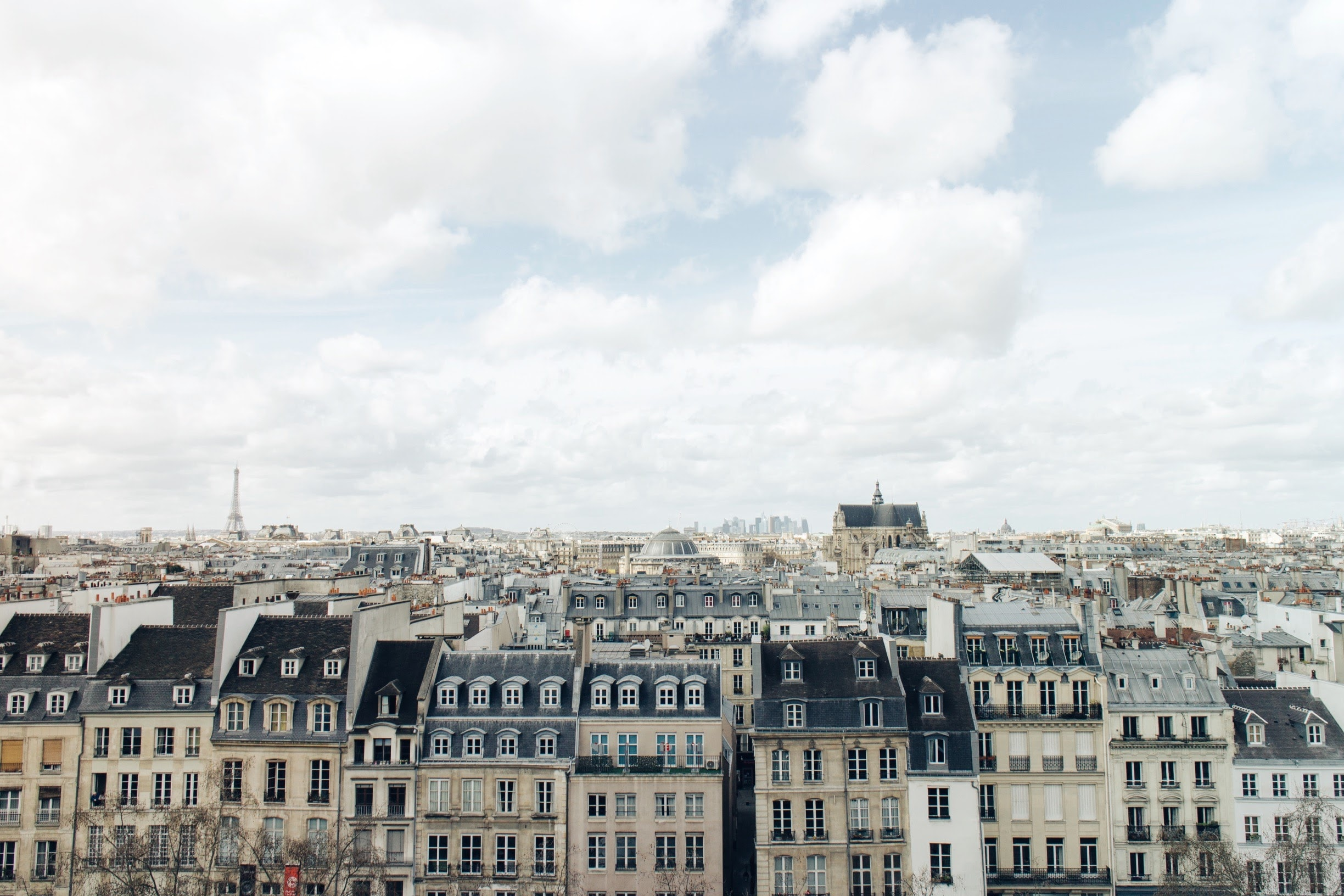 A skyline view of Paris buildings on a bright day with Eiffel Tower in the distance