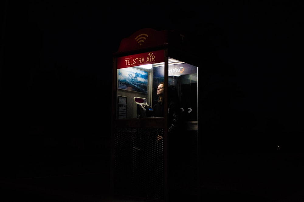 man inside telephone booth