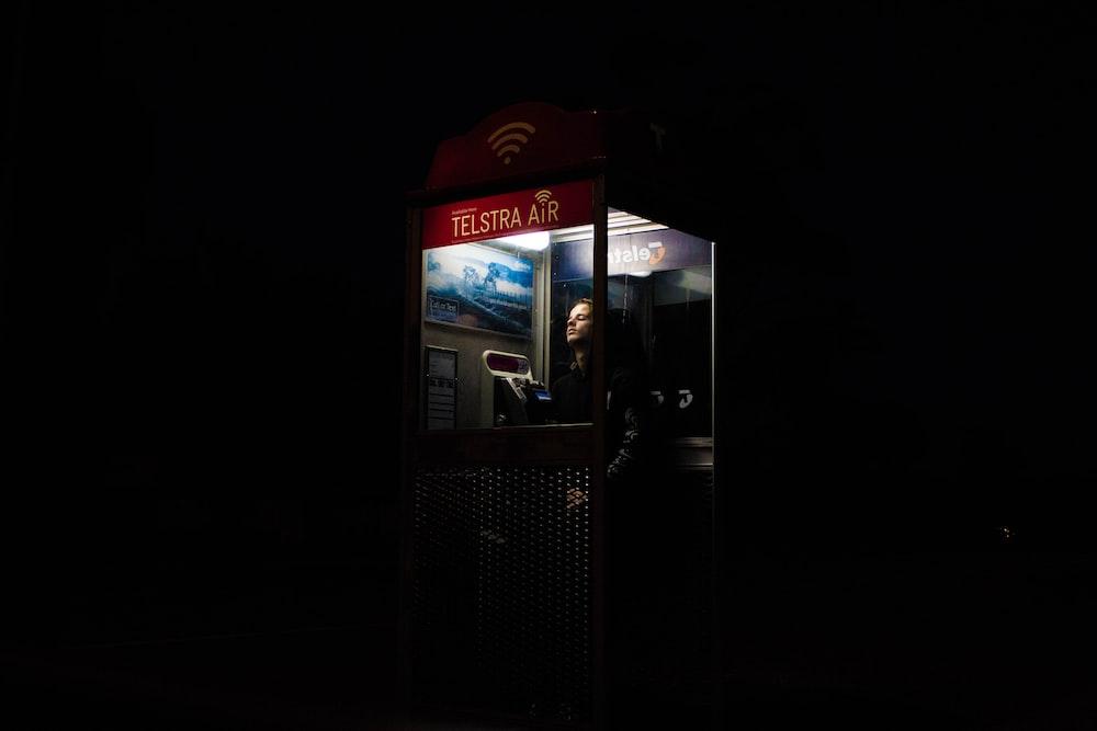 man inside telephone booth