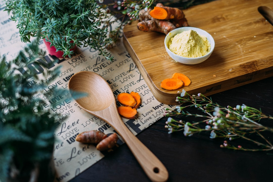 Herbs, turmeric, and spice on cutting board near wooden spoon and paper reading love