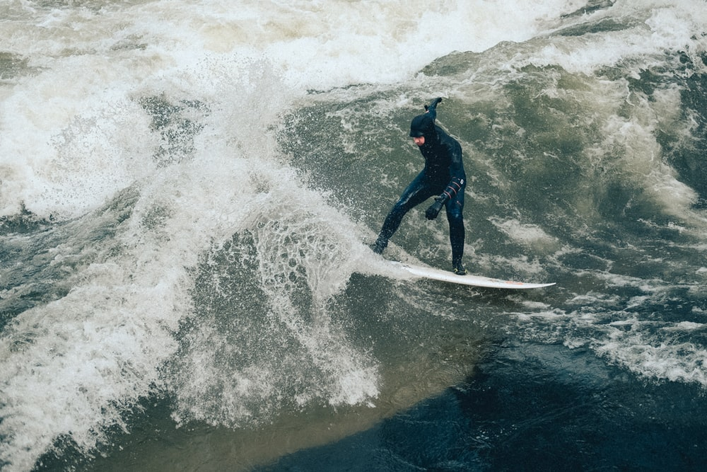 man on white surfboard while surfing