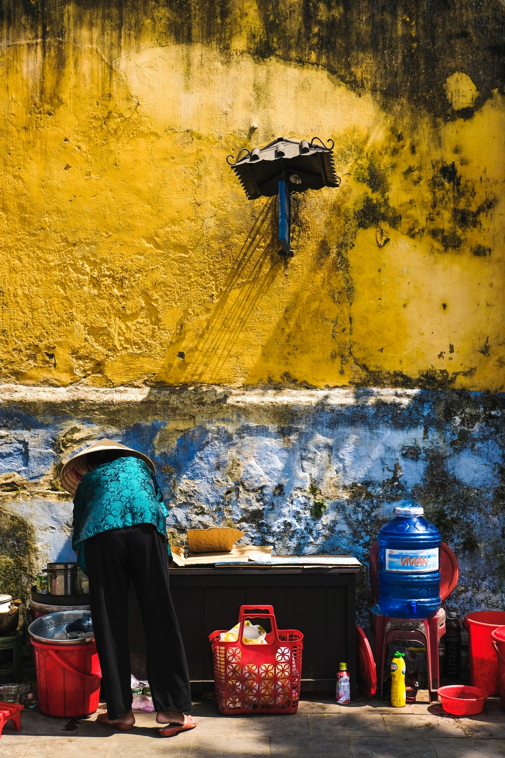 photo of person wearing hat facing wall