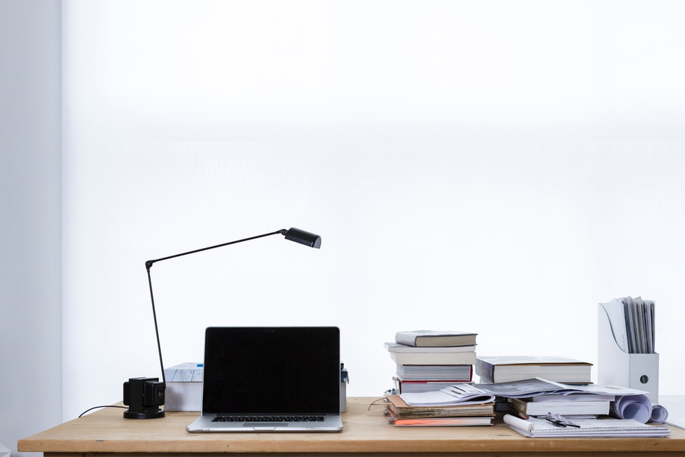 Laptop And Lamp On Desk With Stacks Of Books Files