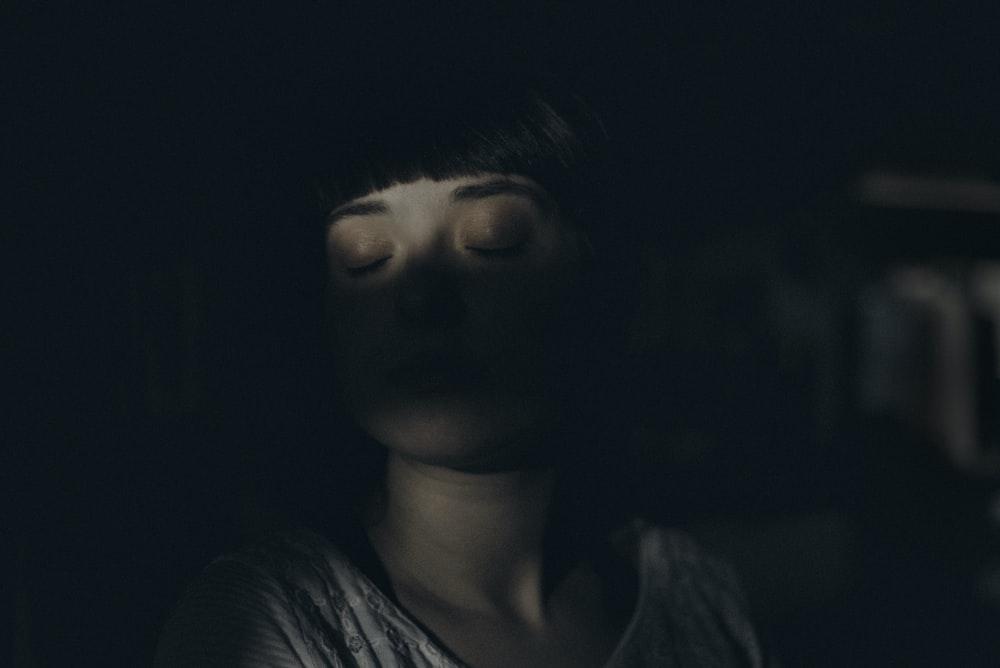 woman sitting inside dark room