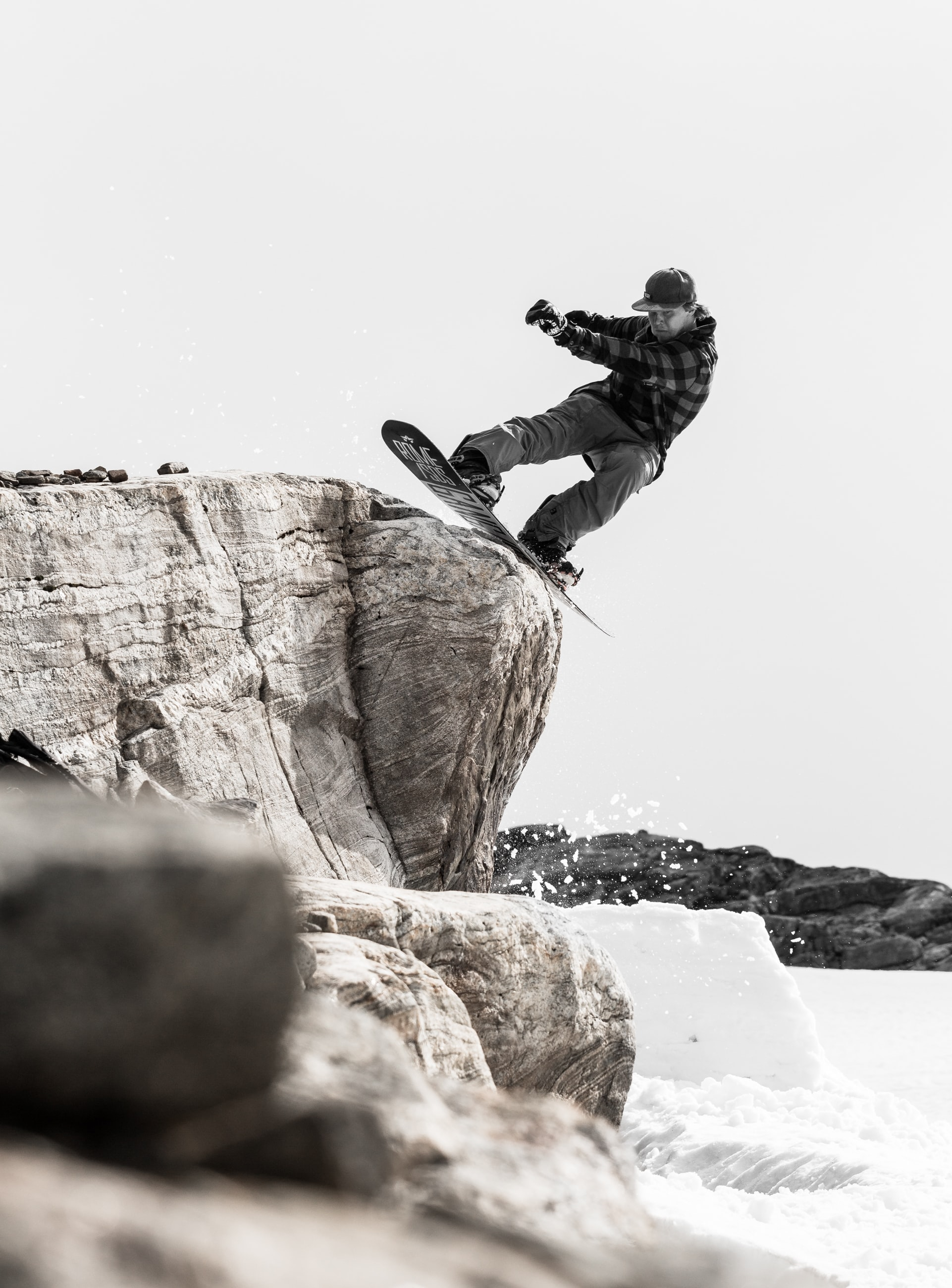 A snowboarder performs a trick and stalls on a boulder on a snowy mountain