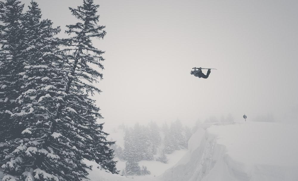 man jump on snow mountain using ski blades