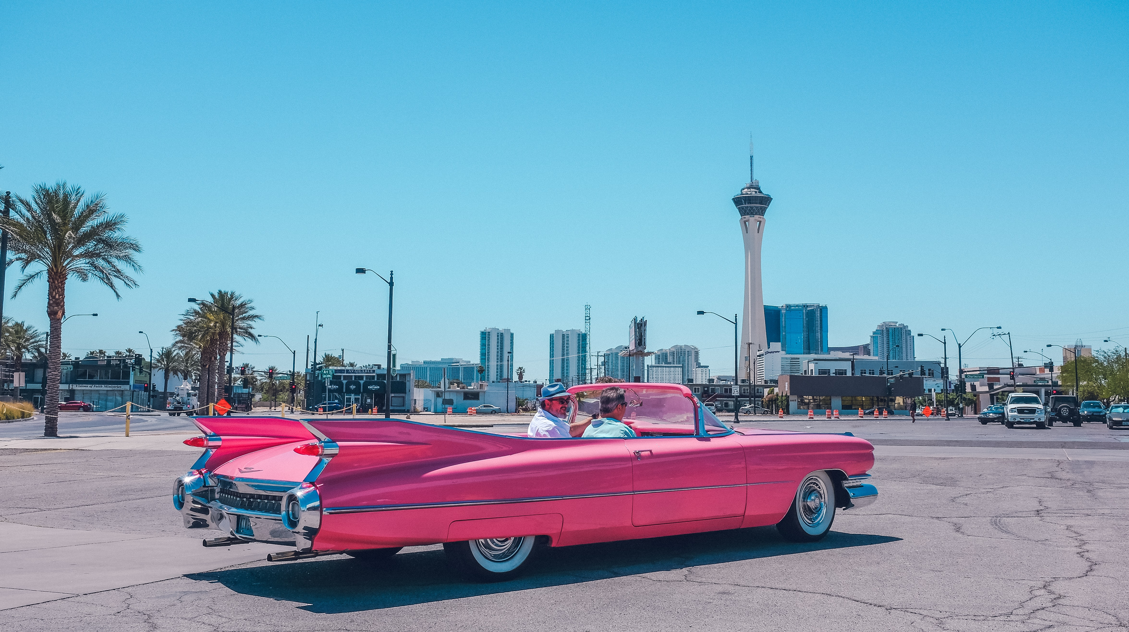 Pink vintage Cadillac car on pavement on clear day in Arts District with tower on skyline