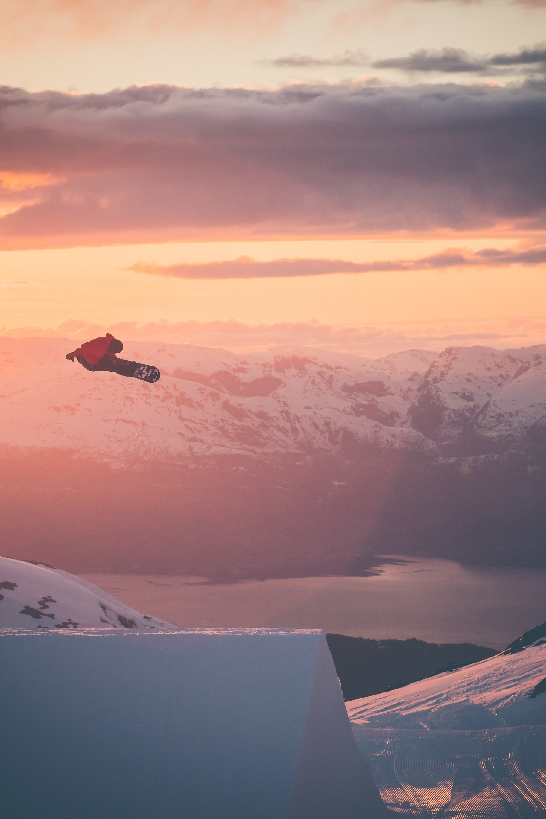 A snowboarder is airborne surrounded by golden skies and snowy mountains