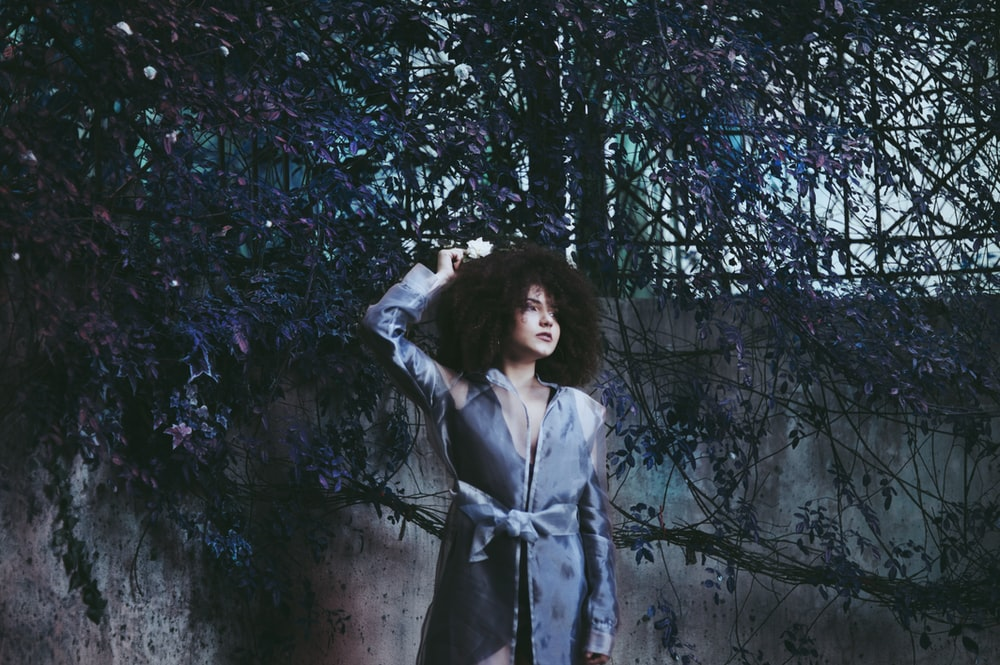 woman posing near wall with tree