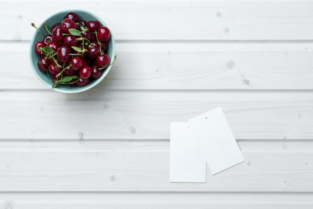 cherries in bowl beside paper